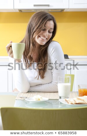 Woman holding a cup of coffee in her kitchen stock photo © wavebreak_media