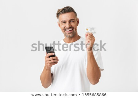 photo of european man in white shirt holding credit card and sma stock photo © deandrobot