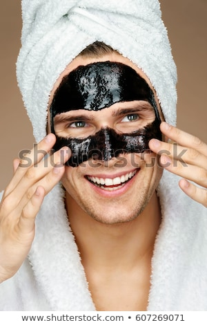 Happy man with black mask on the face. Photo of man receiving spa treatments. Beauty Skin care conce Stock photo © galitskaya