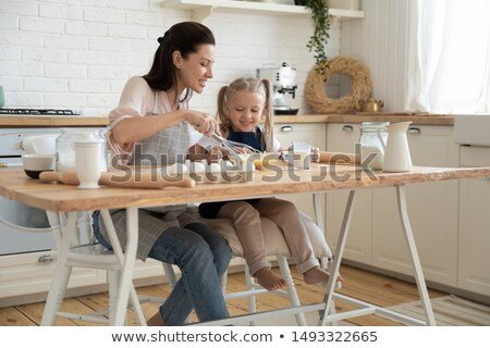 Small cute girl in apron, mixes ingredients, whisks with beater, uses eggs, milk, flour, tries new r Stock photo © vkstudio