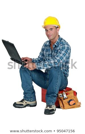 Handlowiec posiedzenia przybornik za pomocą laptopa budowy laptop Zdjęcia stock © photography33