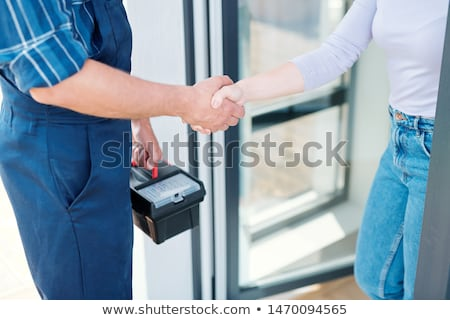 Young woman shaking hand of master while repairman leaving Stock photo © pressmaster