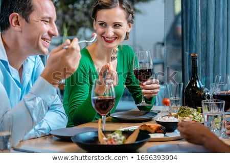 People having fun eating and drinking in a upscale restaurant Stock photo © Kzenon