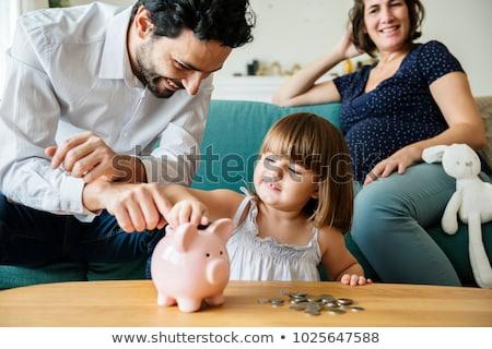 Szczęśliwy ojciec baby banku piggy domu rodziny Zdjęcia stock © dolgachov