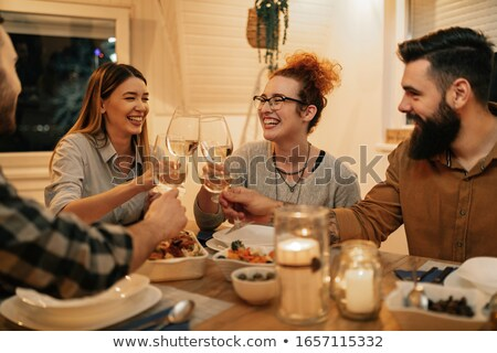 young friends having dinner at home and toasting with white wine stock photo © boggy