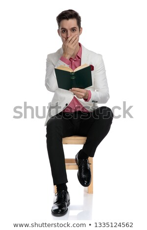 shocked elegant man sitting and reading a thrilling book Stock photo © feedough