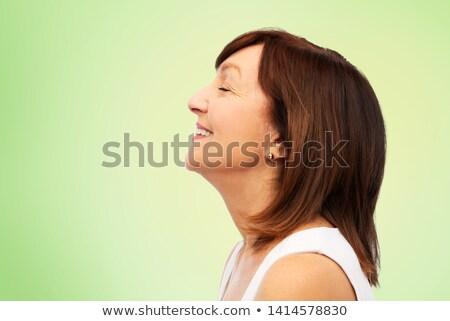 profile of smiling senior woman over lime green Stock photo © dolgachov