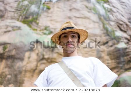 Young man enjoying in natural park at the base of large waterfal stock photo © zurijeta