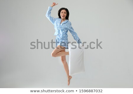 happy woman in pajama jumping with pillow Stock photo © dolgachov