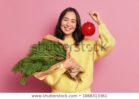 Smiling woman wears red knitted sweater holds glass ball as deco Stock photo © vkstudio