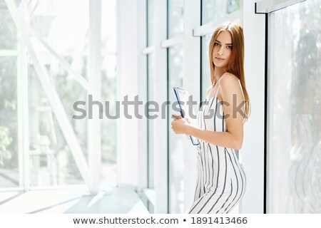 Smiling corporate woman posing with clipboard Stock photo © stockyimages