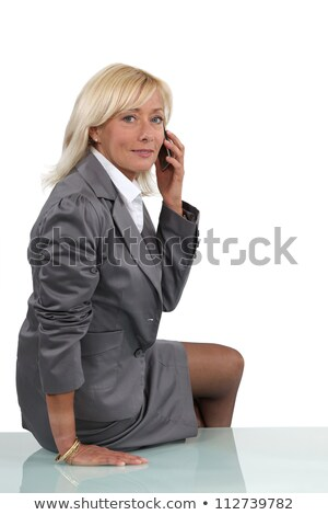 Senior businesswoman perched on desk during call Stock photo © photography33
