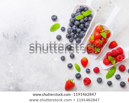 fresh organic raw blueberries in white scoop spoon with leaf on stone kitchen table background stock photo © denismart