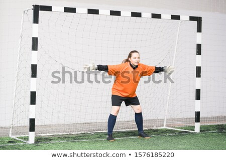 Young female goal keeper in sports uniform and gloves standing in gate Stock photo © pressmaster