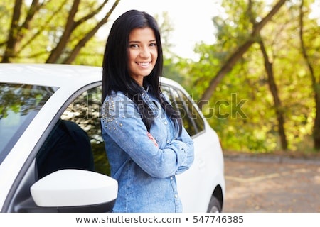 Stock photo: Young, attractive, happy woman standing by her car