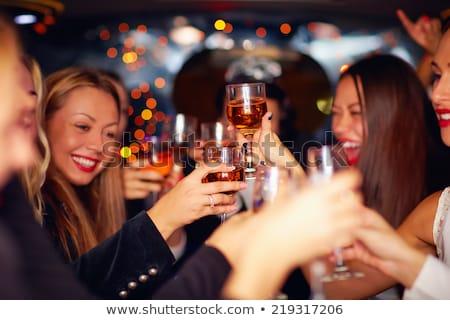 happy women clinking glasses at night club Stock photo © dolgachov