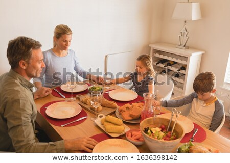 High angle view of family praying before having food on dining table at home Stock photo © wavebreak_media