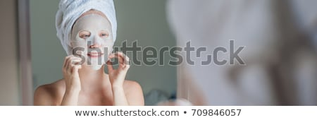 Young red-haired woman doing facial mask sheet stock photo © galitskaya