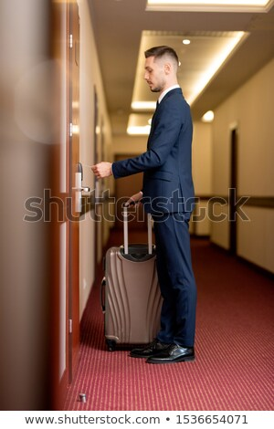 Stockfoto: Young Elegant Businessman With Suitcase Standing In Front Of Closed Door