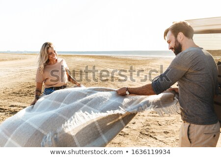 loving couple outdoors near car with mat litter at the beach stock photo © deandrobot
