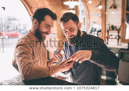 man with smartphone at barbershop or hair salon Stock photo © dolgachov