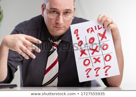 Despondent man holding up a tic-tac-toe game Stock photo © Giulio_Fornasar