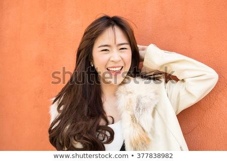 Optimista ázsiai fiatal nő narancs fotó mosolyog Stock fotó © deandrobot