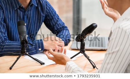 Asian woman radio hosts gesturing to microphone while interviewi Stock photo © snowing