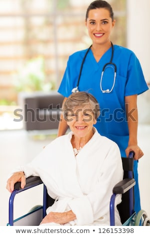 Stock photo: Young woman pushing an elderly lady in a wheelchair