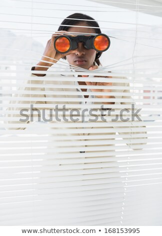 woman looking through the blinds with binoculars Stock photo © photography33