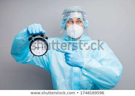 Shocked young guy holding alarm clock Stock photo © stockyimages