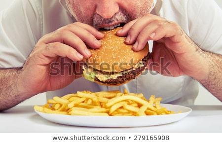 Férfi eszik sajtburger étel kék kenyér Stock fotó © photography33