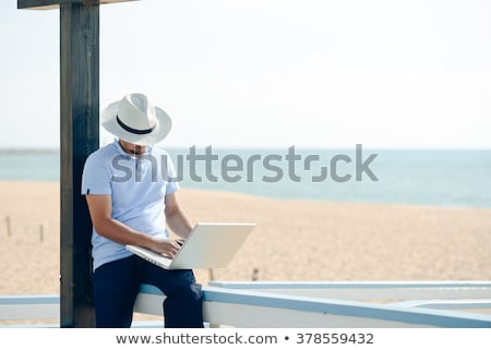excited businessman sitting on a bench in park with laptop stock photo © jakubzak