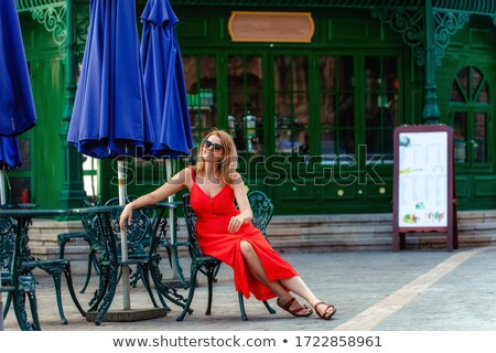 young woman in evening dress posing in a red chair stock photo © filipw