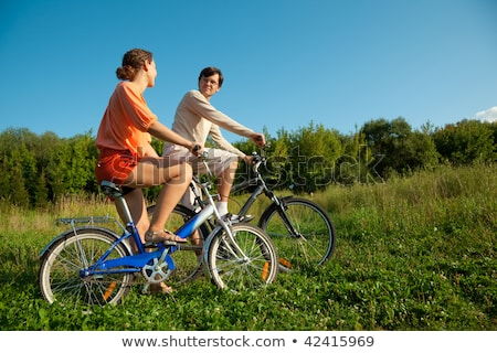 the girl and the man go for a drive on bicycles in a sunny day stock photo © paha_l