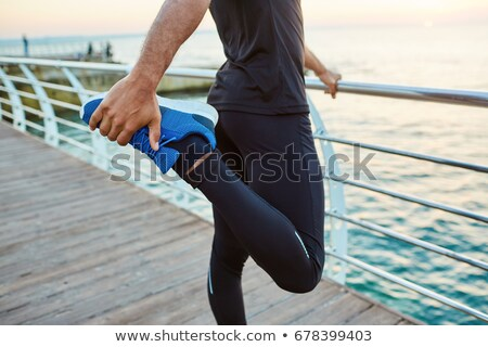 young sportsman stretching his quadriceps stock photo © nito