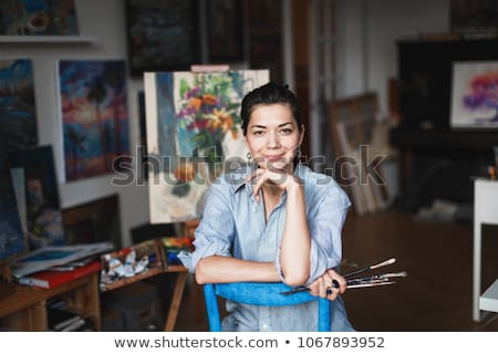 Smiling beautiful woman painter painting with oil paints on blank Stock photo © deandrobot