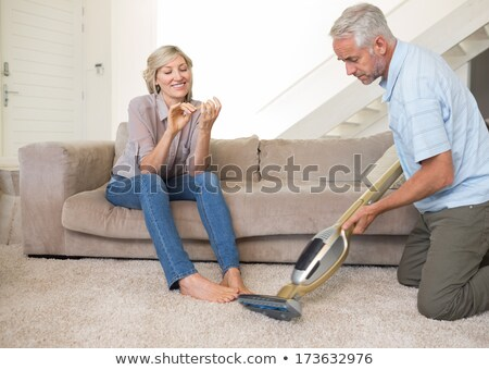 A man dusting and a woman relaxing  Stock photo © IS2