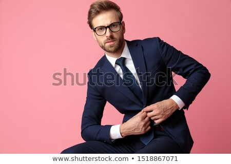 attractive seated businessman buttoning his navy suit Stock photo © feedough