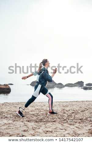 Photo from back of athletic disabled girl with prosthetic leg in Stock photo © deandrobot