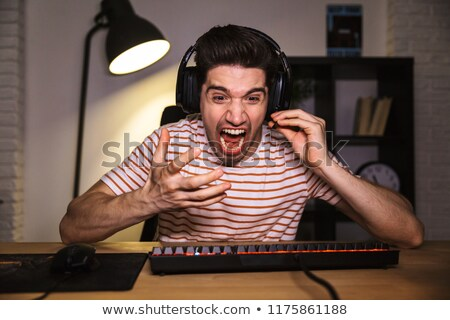 Portrait of stressed young man 20s wearing headset yelling, whil Stock photo © deandrobot