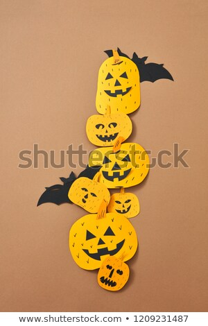 Pattern of paper handcraft pumpkins with scary faces on a brown background with copy space. Composit Stock photo © artjazz