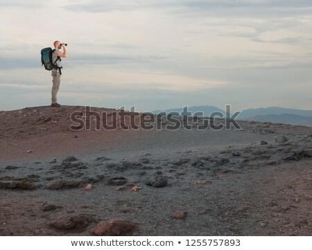 Explorer with binocular searches something in a desert Stock photo © alphaspirit