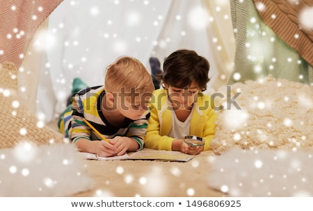 boy with magnifier and map in kids tent at home Stock photo © dolgachov