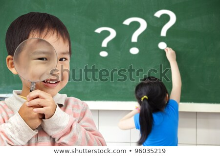 little girl writing question marks on chalkboard stock photo © andreypopov
