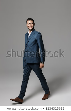 Full length image of unshaved arabic man 30s in formal suit walk Stock photo © deandrobot