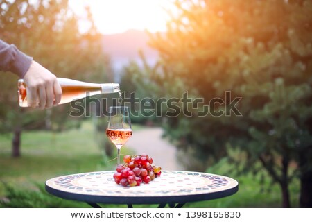 Stockfoto: Man Pouring Rose Wine To The Glass In Autumn Vineyard On Marble