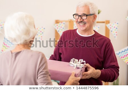 Happy retired man taking giftbox with present given by his wife Stock photo © pressmaster