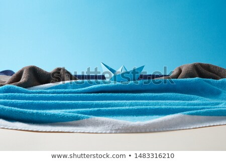 Waves of blue sea made from beach towel with paper boat. Stock photo © artjazz