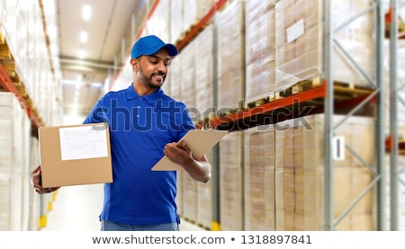 indian delivery man with clipboard at warehouse stock photo © dolgachov